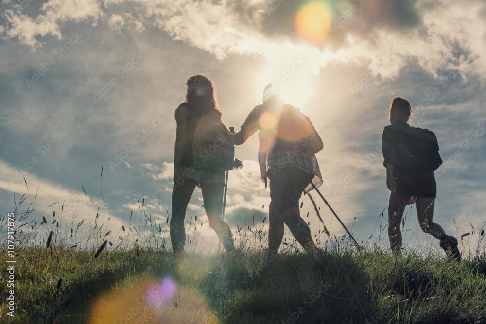 Fototapeta Three friends walk on mountain path in sunny day