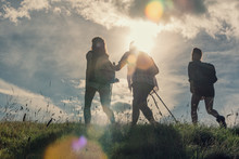 Three Friends Walk On Mountain Path In Sunny Day