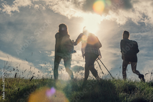 Foto  Three friends walk on mountain path in sunny day