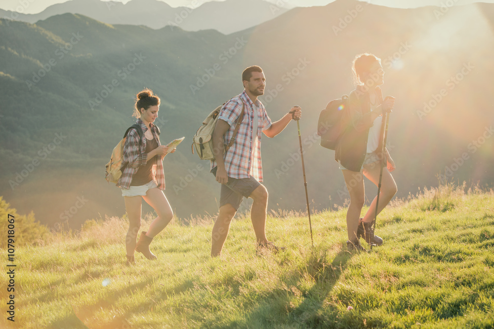 Fototapety, obrazy: Three friends walk on mountain path in sunny day