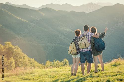 Fotografie, Obraz  Three friends stand looking at panorama on mountain