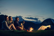 canvas print picture - Three friends camping with fire on mountain at sunset