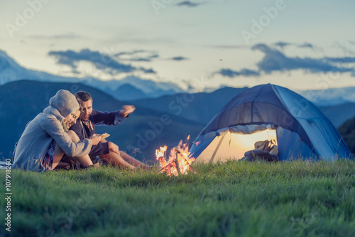 Fotografering Three friends camping with fire on mountain at sunset