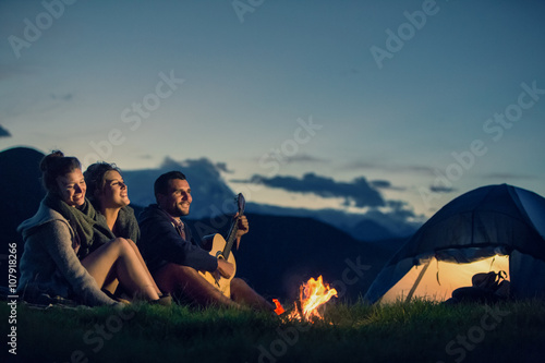 Three friends camping with fire on mountain at sunset Fotobehang
