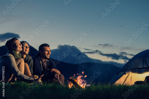 Three friends camping with fire on mountain at sunset
