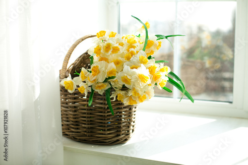 Deurstickers Narcis daffodils in a wicker basket sitting on the windowsill
