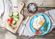 Breakfast set. Whole grain sandwich with fried egg, vegetables and herbs
