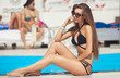 beautiful woman in bikini and sunlasses sitting in swimming pool with cocktail. Fashionable portrait. Elegant woman in a bikini and sunglasses