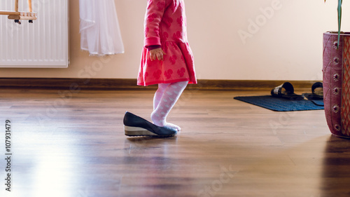 dziecko zakłada buty swojej mamy