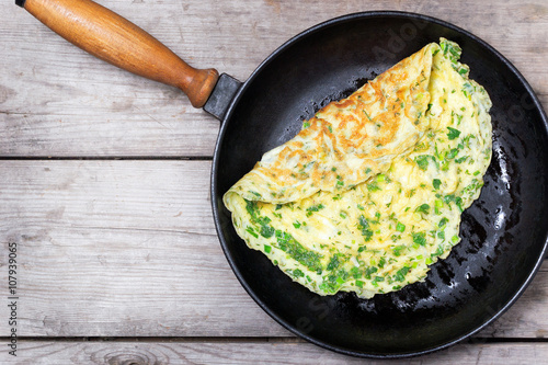 French omelet with herbs, cooked in cast iron skillet