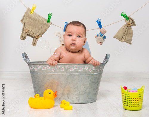 baby girl bathes in a trough