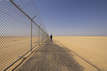 A Man Walking In The Side Way Next To The Border Fence