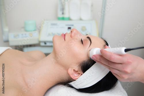 Fotografie, Obraz  Schöne junge Frau macht Ultraschall Hautreinigung und Gesichtsbehandlung bei Kos