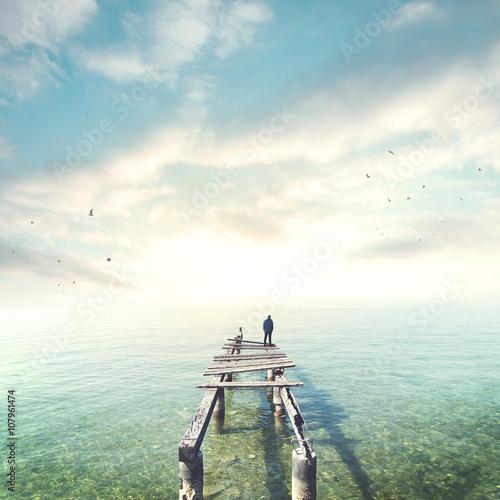 Foto  Man observing the sea on a boardwalk