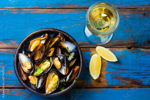 Valokuva  Mussels in clay bowl, glass of white wine and lemon