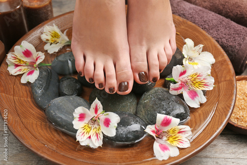 Foto op Plexiglas Manicured female feet in spa wooden bowl with flowers and water closeup