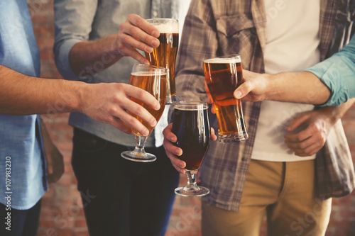 Vászonkép  Male group clinking glasses of dark and light beer on brick wall background