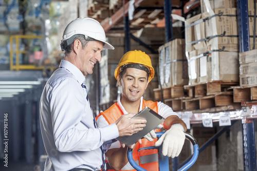 Floor supervisor consulting with forklift operator Fototapeta