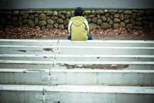 Back Of Lonely Child Sitting On Bench