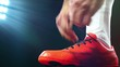 Football, soccer game. Professional footballer buckle his red shoes, black background