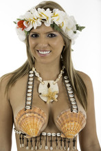 Pretty Woman Dressed In Hawaiian Costume Made Of Sea Shells And Wearing A Lei. Looking At Camera Smiling Shot On White Background.