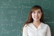 beautiful girl teacher with green blackboard