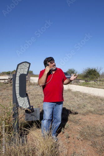 Fotografie, Obraz  Man using landline telephone in the middle of no where in Texas