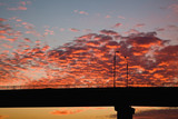 sunset over the bridge, blue yellow orange sky, orange clouds cirrus