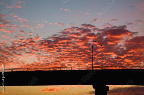 sunset over the bridge, blue yellow orange sky, orange clouds cirrus