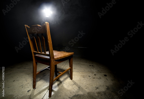 Fotografie, Obraz  Isolated wooden chair in a dark scary prison with an interrogation spotlight
