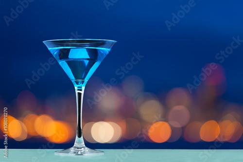 Pinturas sobre lienzo  Glass of martini standing against city lights