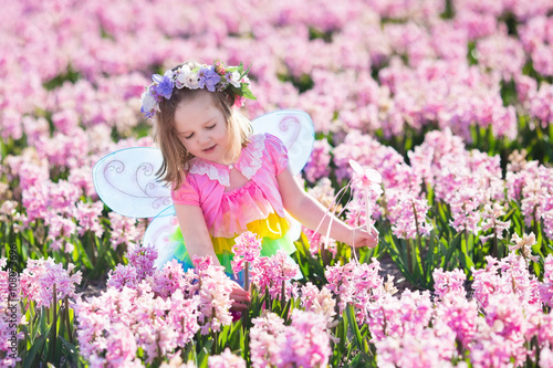 Beautiful Girl Playing In Blooming Hyacinth Flower Field. Kids Princess  Birthday Party With Fairy Costume, Butterfly Wings And Magic Wand.