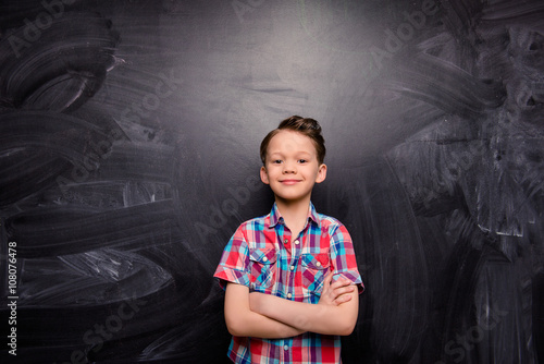 Little boy with crossed hands on the background of blackboard Wallpaper Mural