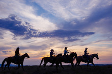Cowgirls And Cowboy Riding Horses At Sunset