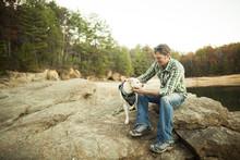 Man Petting Dog On Rocks Near ...