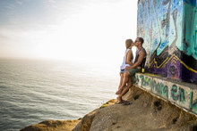 Caucasian Couple Kissing At Mural On Cliff