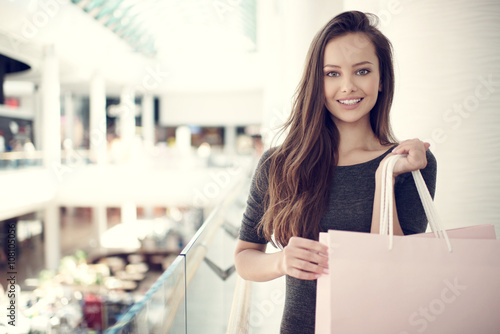 obraz lub plakat Beautiful woman with shopping bags in big mall.