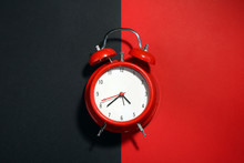 New Red Clockwork Alarm Clock On A Black And Red Background