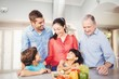 Cheerful family standing by kitchen table