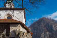 Kamnik, Slovenia - January 25, 2016. Small Castle Entrance, Firstly Mentioned In 1202, And The Hill On The Background Of Blue Sky.