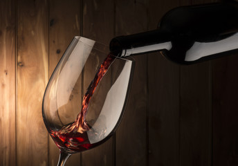 Fototapeta Wino glass with red wine on wooden background