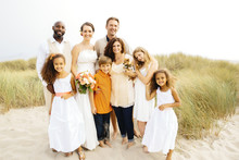 Bride And Groom Smiling With Family At Wedding