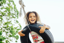 Mixed Race Girl Smiling In Tire Swing
