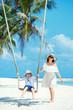 Young beautiful woman swinging son on a tropical beach, Koh Phangan island. Thailand.