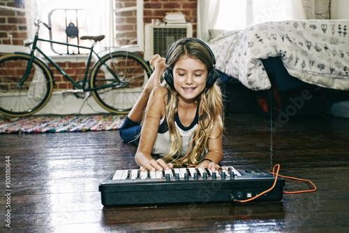 Native American girl playing keyboard in bedroom
