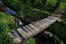 Small Plank Bridge Across Water Conduit Painted As Piano Keys.