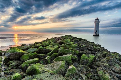 Montage in der Fensternische Leuchtturm Lighthouse with moody dramatic clouds at sunset with algae rocks. New Brighton, Merseyside, UK.
