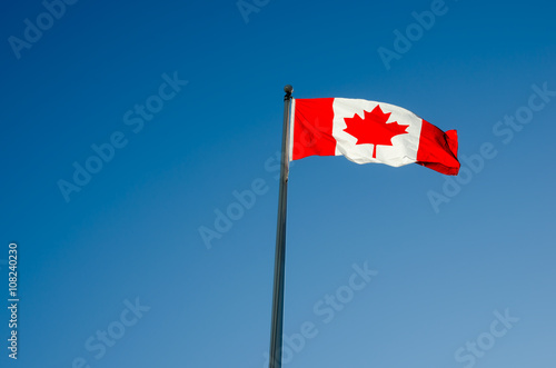Canadian flag waving over blue sky