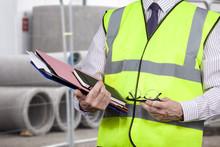 Building Surveyor In High Visibility Vest Carrying Work Folders