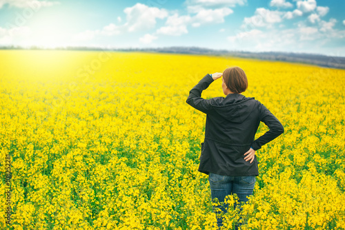 Poster Geel Woman agronomist standing in field of blooming cultivated rapese